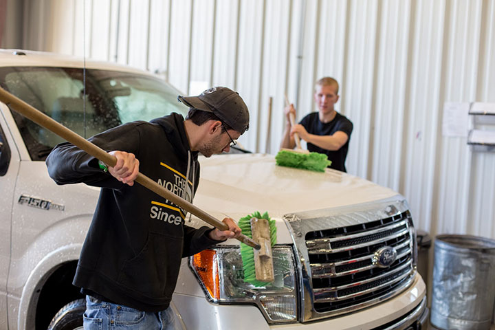 employees washing a truck after repairs were made